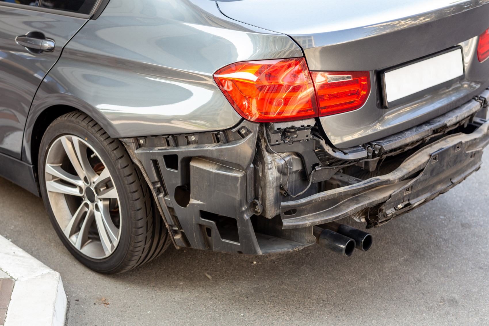 Tail of modern car with removed rear bumper. Vehicle after traffic accident and crash. Transport repair and insurance
